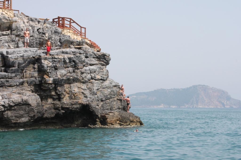 Люди прыгают со скал в море фото